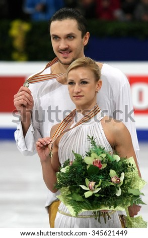 BUDAPEST, HUNGARY - JANUARY 19, 2014: Tatiana VOLOSOZHAR / Maxim TRANKOV of Russia pose at the victory ceremony at ISU European Figure Skating Championship in Syma Hall Arena. - stock photo