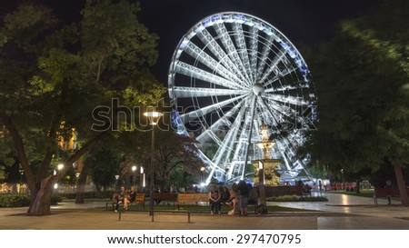 BUDAPEST, HUNGARY, JULY 9, 2015: Erzsebet ter is the largest green area in Budapest's inner city. Danubius fountain and Sziget's Eye (ferriswheel) can be seen at the background. - stock photo