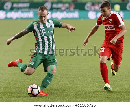 BUDAPEST, HUNGARY - JULY 30, 2016: Gergo Lovrencsics (L) of FTC crosses the ball next to Milan Nemes #33 of DVTK during the OTP Bank Liga match between Ferencvarosi TC and DVTK at Groupama Arena.