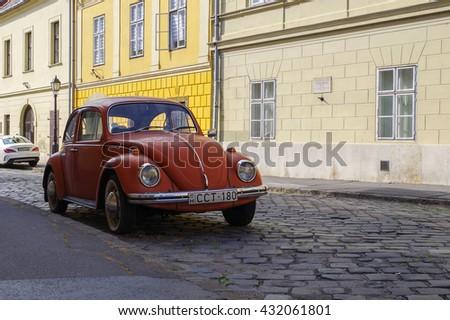 Budapest, Hungary - July 9, 2015: Orange retro economy car - Volkswagen Beetle parked on the old street of Budapest.  - stock photo
