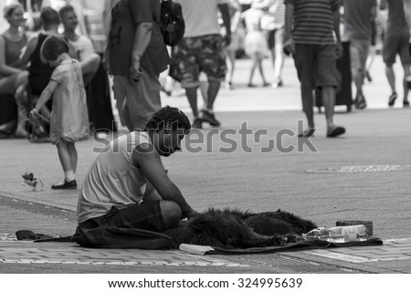 Budapest,Hungary - July 26-07-2015 - Poor homeless men is sitting on the street next to his dog. Behind the men a little girl is playing with her puppet dog toy. - stock photo