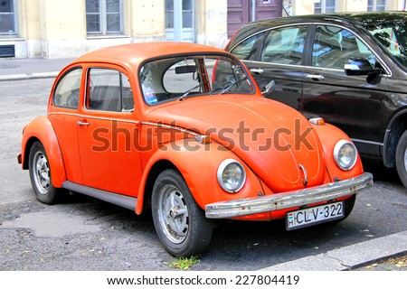 BUDAPEST, HUNGARY - JULY 23, 2014: Red classic vintage car Volkswagen Beetle at the city street. - stock photo