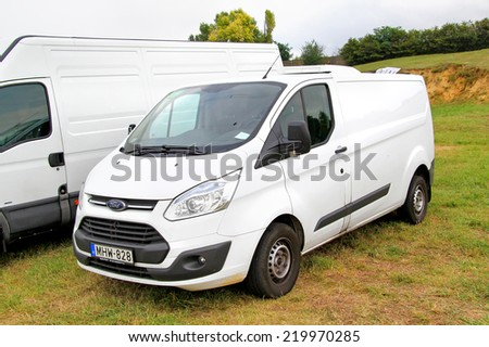 BUDAPEST, HUNGARY - JULY 27, 2014: White cargo van Ford Transit at the grass field. - stock photo