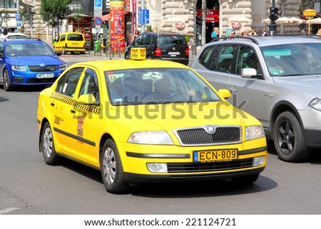 BUDAPEST, HUNGARY - JULY 23, 2014: Yellow taxi car Skoda Octavia at the city street. - stock photo