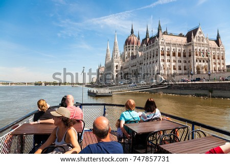 Budapest, Hungary - 2017, May 29 : Tourists on a boat trip on the Danube river next to the Pest river bank with the famous parliament building, Budapest