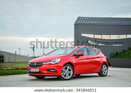 BUDAPEST, HUNGARY - NOVEMBER 27, 2015: 2016 model year Opel Astra (generation K) at the test-drive. Red hatchback Opel Astra is equipped with headlights that consist of 16 individual matrix LED. - stock photo