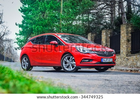 BUDAPEST, HUNGARY - NOVEMBER 27, 2015: 2016 model year Opel Astra (generation K) is on display. Red hatchback Opel Astra is equipped with headlights that consist of 16 individual matrix LED. - stock photo