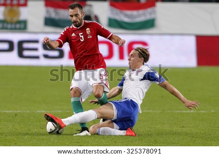 BUDAPEST, HUNGARY - OCTOBER 8, 2015: Hungarian Attila Fiola (l) is tackled by Faroese Joan Edmundsson during Hungary vs. Faroe Islands UEFA Euro 2016 qualifier football match in Groupama Arena. - stock photo