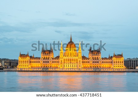 Budapest Parliament at dusk on the Danube river in Hungary. - stock photo