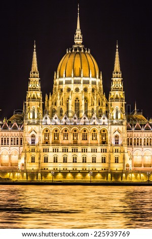Budapest Parliament in Hungary at night, reflections on the Danube river waters. - stock photo