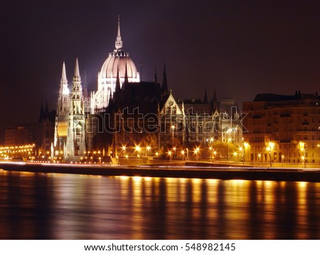 Budapest parliament side view, from across the Danube river, night long exposure, city lights reflection, tower dome lights