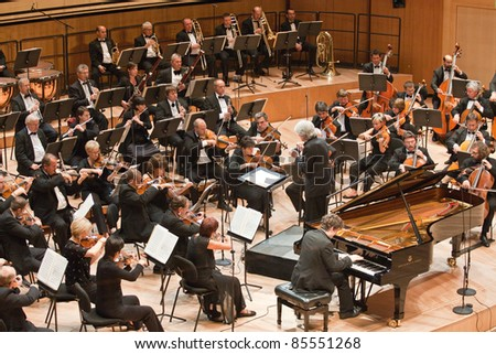"BUDAPEST - SEPT 18: Magyar Radio Symphonic Orchestra perform on concert at ""Palace of Art"" Budapest Sept 18, 2011 in Budapest, Hungary. Conductor: Gergely Vajda, pianist: Namoradze Nicolas"