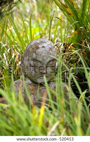 Budda in grass - stock photo