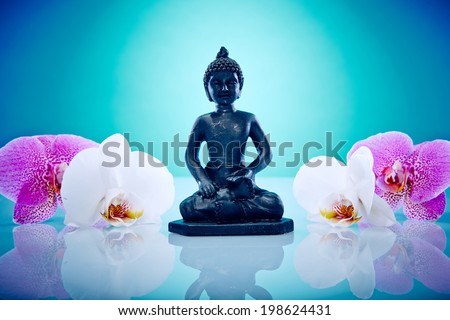 Buddah in middle of pink and white orchis Wellness and Spa Image, works perfect for advertising Health and Beauty, Spirituality or Massage. - stock photo