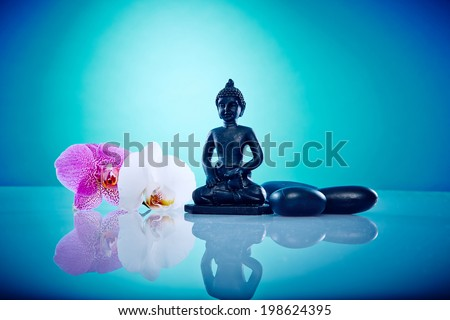 Buddah next to orchis and hot stones Wellness and Spa Image, works perfect for advertising Health and Beauty, Spirituality or Massage. - stock photo