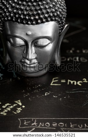 buddha and gold coins on a table - stock photo