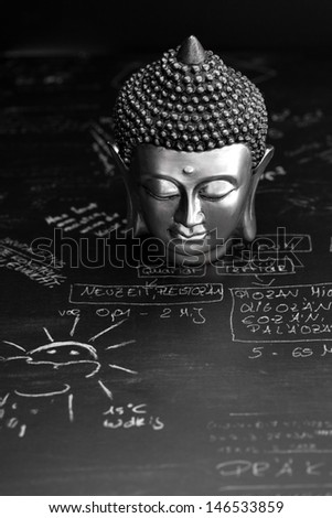 buddha and gold coins on desk  - stock photo