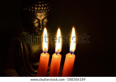 buddha behind candles (warm atmosphere) - stock photo