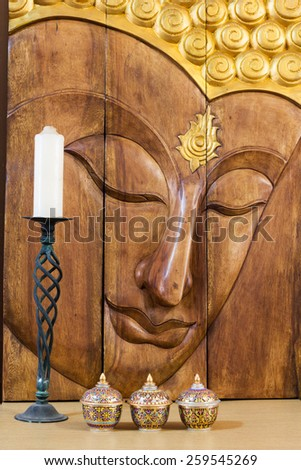 buddha face carving, thai colorful handcraft bowls, white candle on vintage green candlestick for interior concept - stock photo