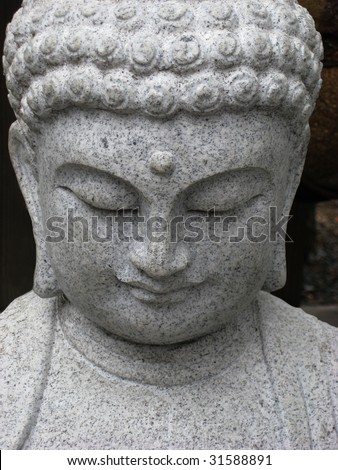 Buddha face looking down - stock photo