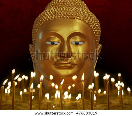 Buddha face with lit candles in temple