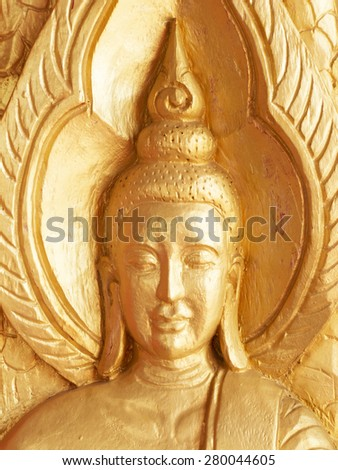Buddha face wooden carving painted  red and gold color on window temple, thailand - stock photo