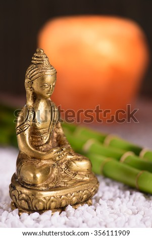 Buddha figure sitting in front of burning candle light