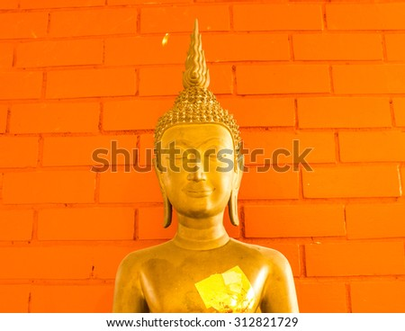 Buddha golden yellow with a brick background.