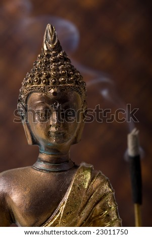 buddha idol with incense sticks, against bamboo background
