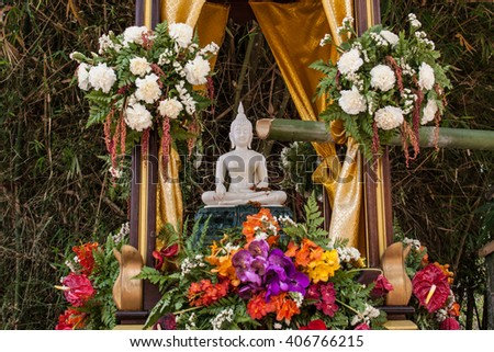 Buddha image and flowers in the annual Buddhist lent songkran festival - stock photo