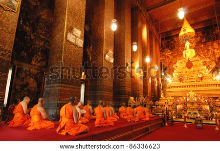 Buddha image and monks in Wat Pho Temple, Bangkok, Thailand - stock photo