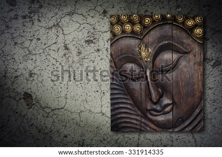 Buddha image in Thai style wood graving on the wall - stock photo