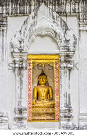 Buddha image statue in grunge concrete wall with Thai stucco decorations frame at Wat Phra Sing Wora Maha Wihan. Wat Phra Sing is a Buddhist temple in Chiang Mai province, Northern Thailand. - stock photo