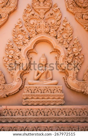 Buddha image with ight hand in front of the chest and Thai traditional carving to decorate the wall of Buddhist church. - stock photo