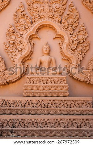 Buddha image with right hand on the knee and Thai traditional carving to decorate the wall of Buddhist church. - stock photo