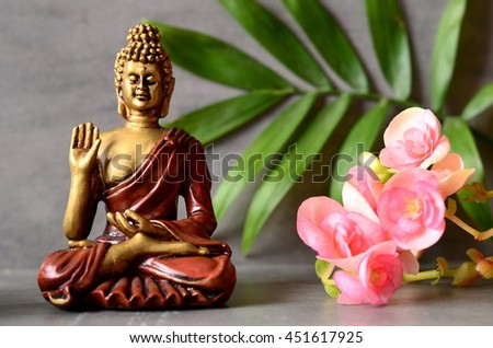Buddha is sitting in ZEN garden with  flower and balance stones. - stock photo