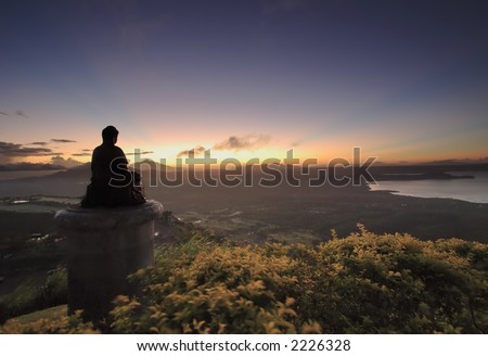 Buddha silhouette looking into the sunrise over the mountains