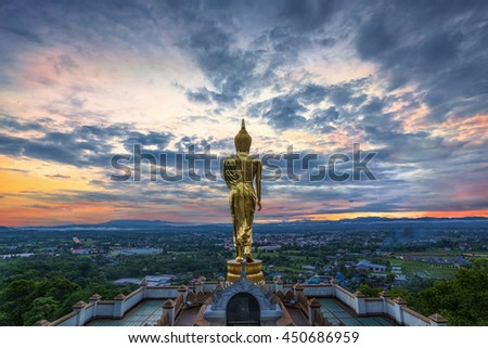 Buddha standing on a mountain at morning Wat Phra That Khao Noi, Nan Province, Thailand - stock photo