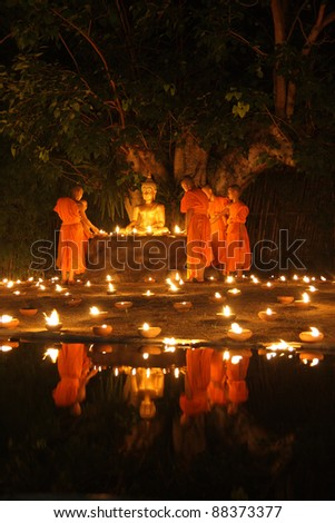 Buddha statue and Buddhist reflect on water with candles fire lighting