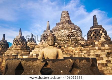 Buddha statue at Borobudur temple at sunset in Yogyakarta, Java, Indonesia. - stock photo