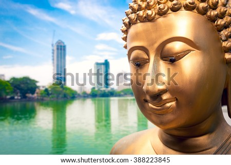 Buddha statue close up and Colombo in background - stock photo