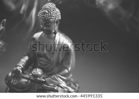 Buddha statue decorated with offerings and flowers. Murti Buddha in the smoke from the incense and floral decorations. Buddhism and its deities, Gautama Buddha wb black and white - stock photo