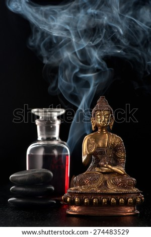 Buddha statue, essential rose oil and stones zen - stock photo