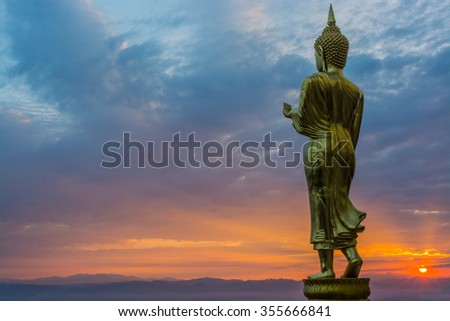 Buddha statue facing cityscape in morning sunrise on mountain top in Nan provincial town, Northern Thailand..