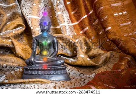 Buddha statue in bronze with Chakras on a silk scarf - stock photo