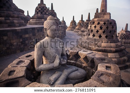 Buddha statue in Buddist temple of Borobudur in the morning. Yogyakarta. Java, Indonesia - stock photo