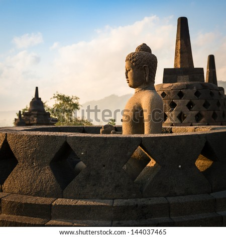 Buddha statue in open stupa in Borobudur, or Barabudur, temple Jogjakarta, Java, Indonesia at sunrise. - stock photo
