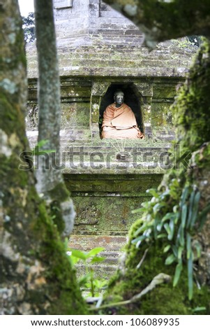 buddha statue in stupa wall seen through tropical trees in Pura Ulun Danu temple lake bratan, bedugal, bali indonesia - stock photo
