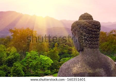 Buddha statue in the morning at Borobudur Temple. Yogyakarta, Central Java, Indonesia. - stock photo