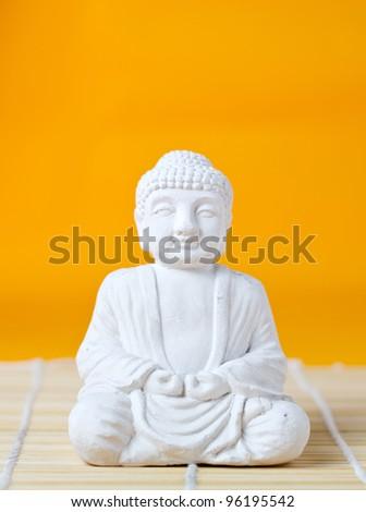 Buddha statue on bamboo mat - stock photo